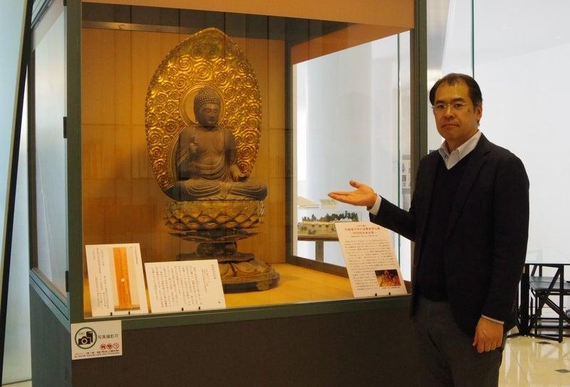 展示されている阿弥陀如来坐像と大河内智之主任学芸員