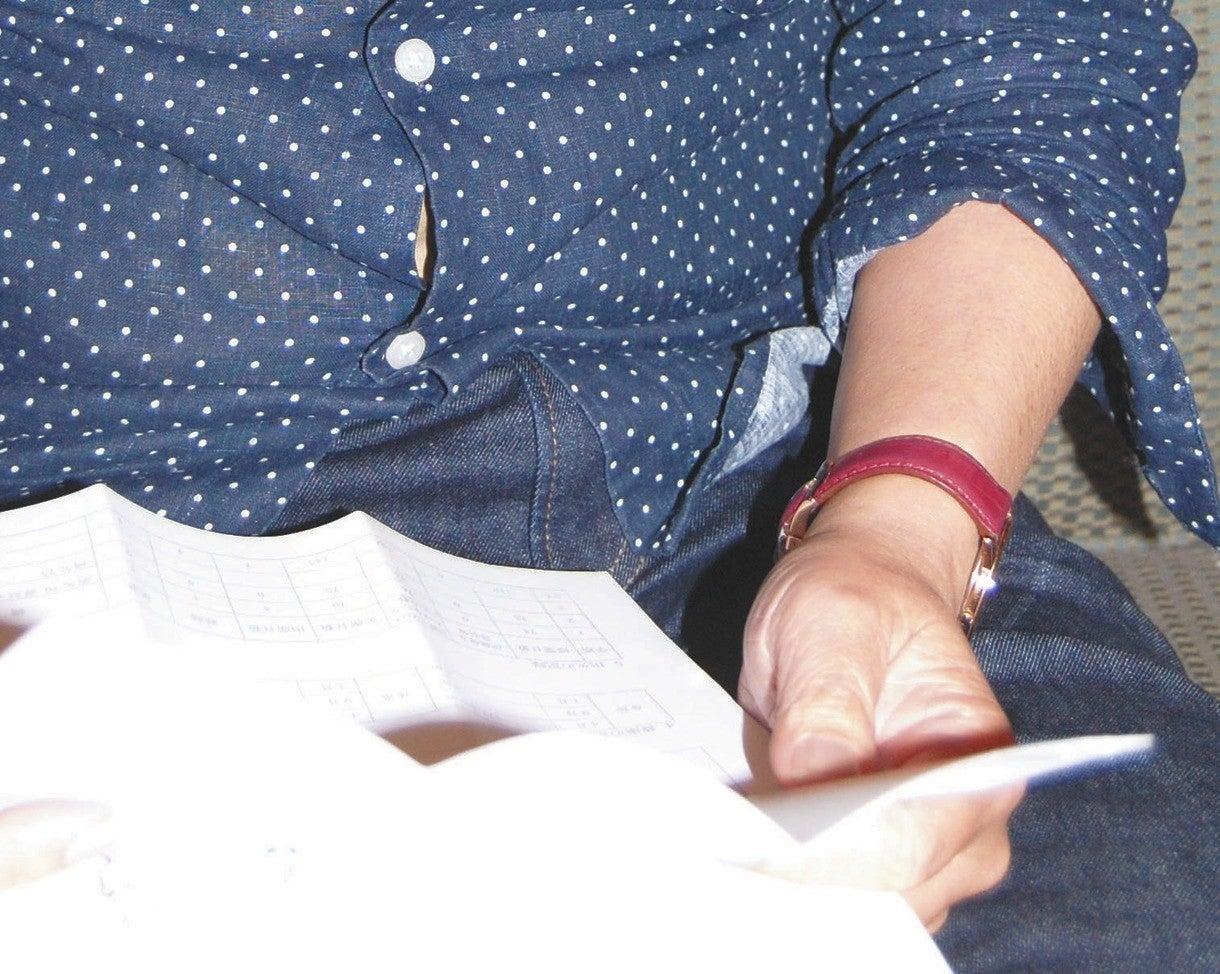 長男の近況を知らせる手紙を読む竹内英治さん。長男の様子が心配になる=東京都内で(一部画像処理)